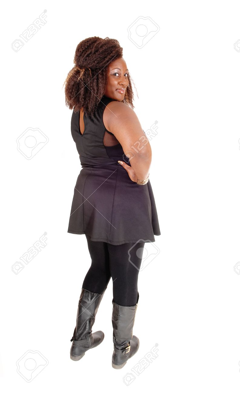 fda2dd5a510fd A big African American woman in a black dress, tights and boots standing  from the