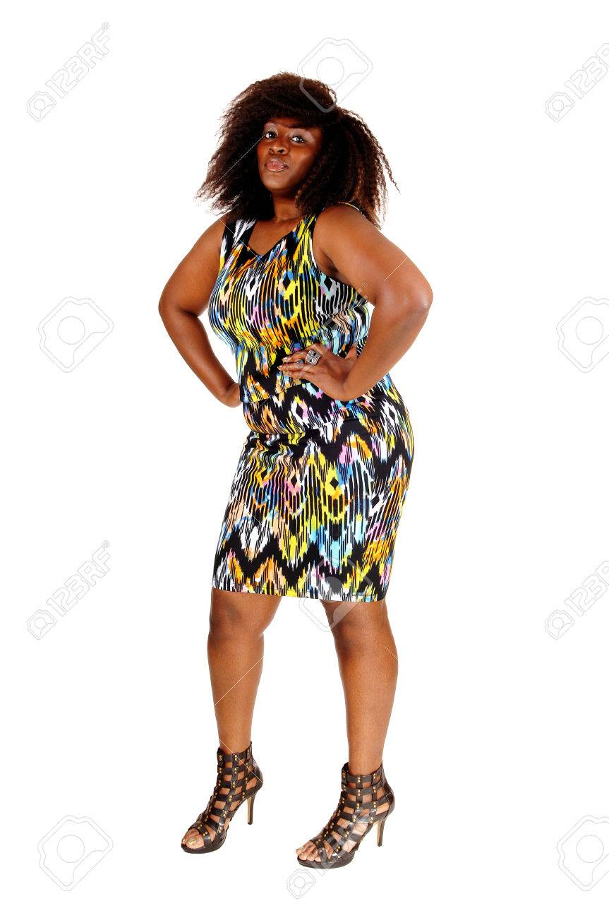 86d7d2ff47366 A tall big African American women in a colourful dress standing from the  front, isolated