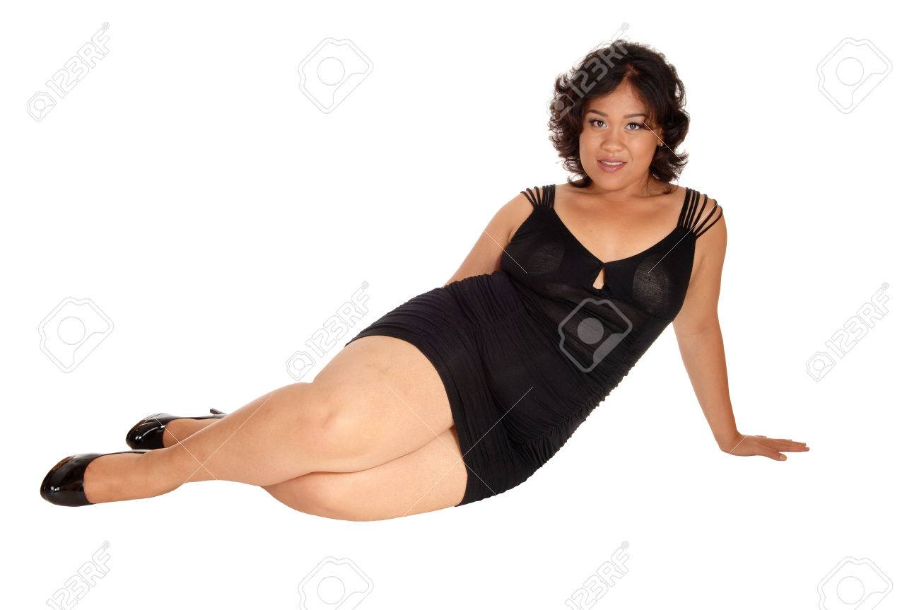 A Young Plus Size Woman Sitting On The Floor In A Short Black ...