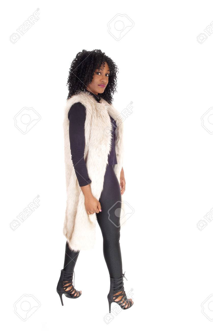 33d73cf8bdc A young African American woman in black tights and a white fur coat with  walking in