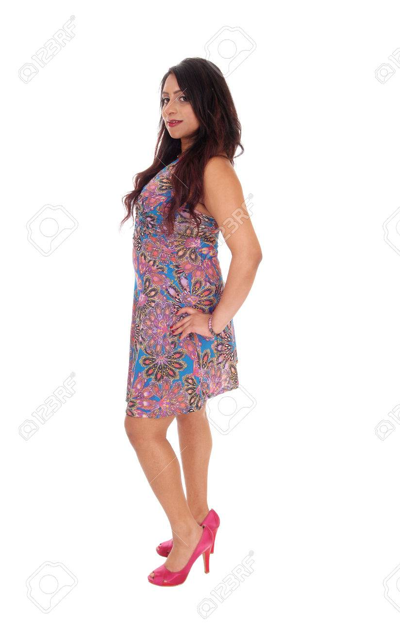 38561e317f1 A beautiful young East Indian woman standing full length in a colorful  summer dress