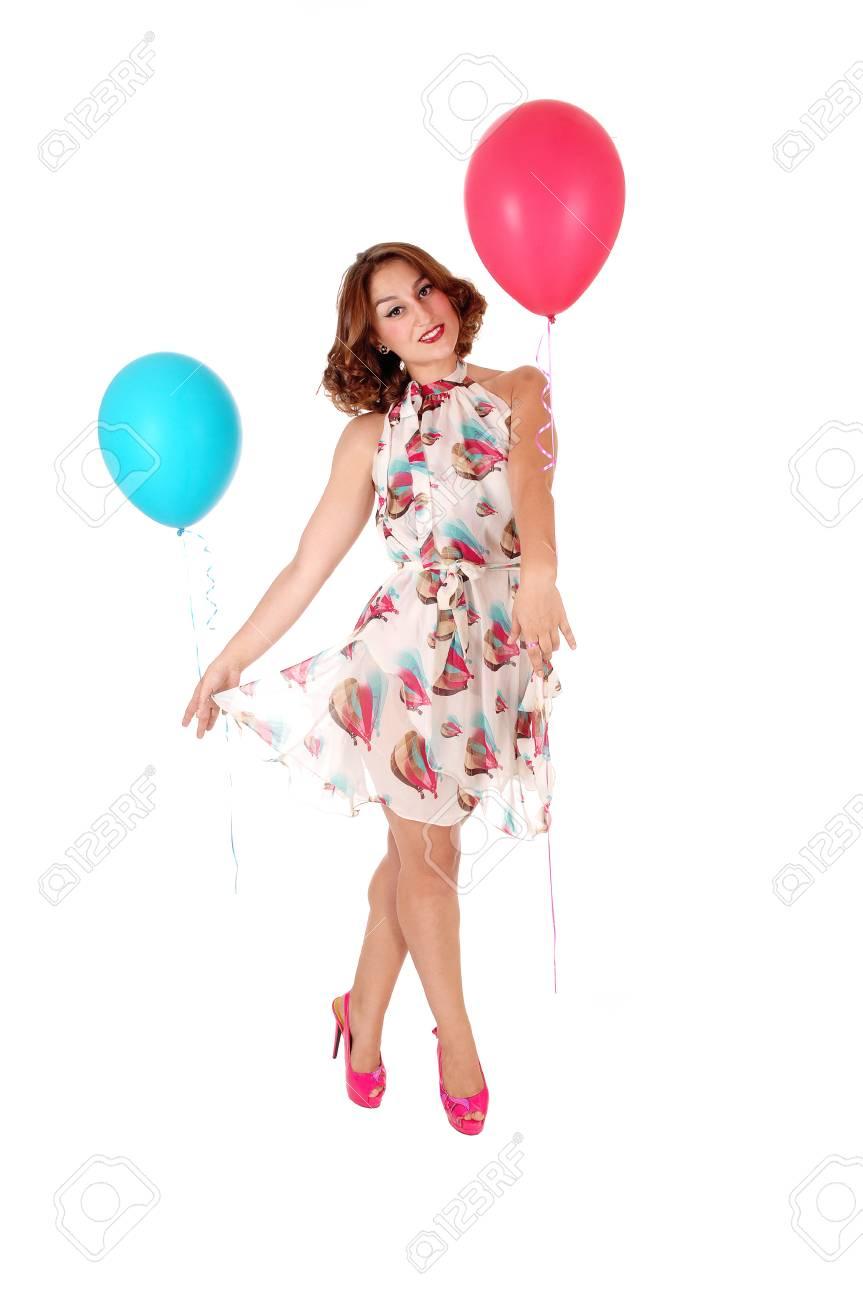 f8873daf3c47 Archivio Fotografico - Una bella giovane donna in un abito estivo e tacchi  tenendo due palloncino e ballando