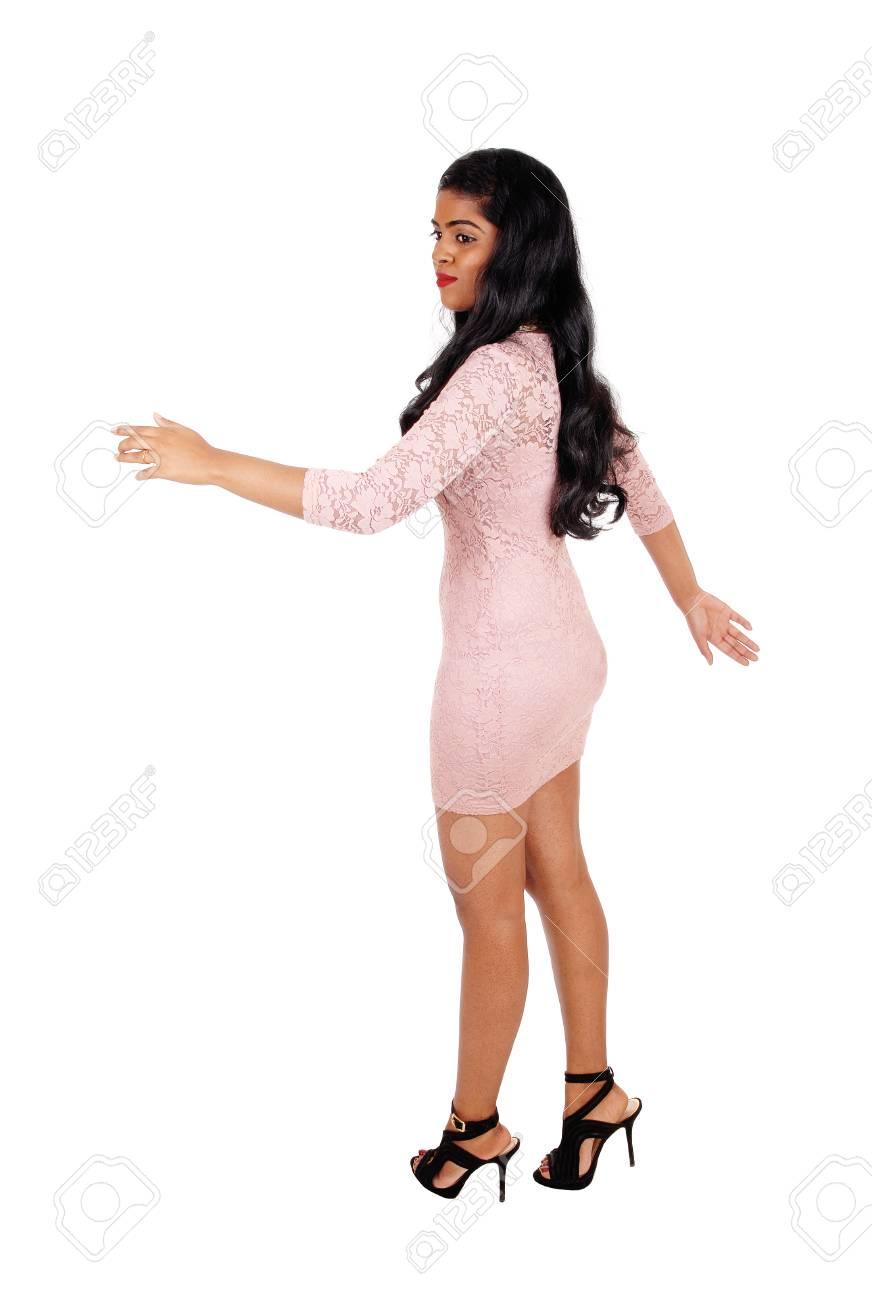 bcd0c1b1f40 Banque d images - Une très belle jeune femme marchant dans une robe  moulante beige et de longs cheveux noirs isolé pour fond blanc.