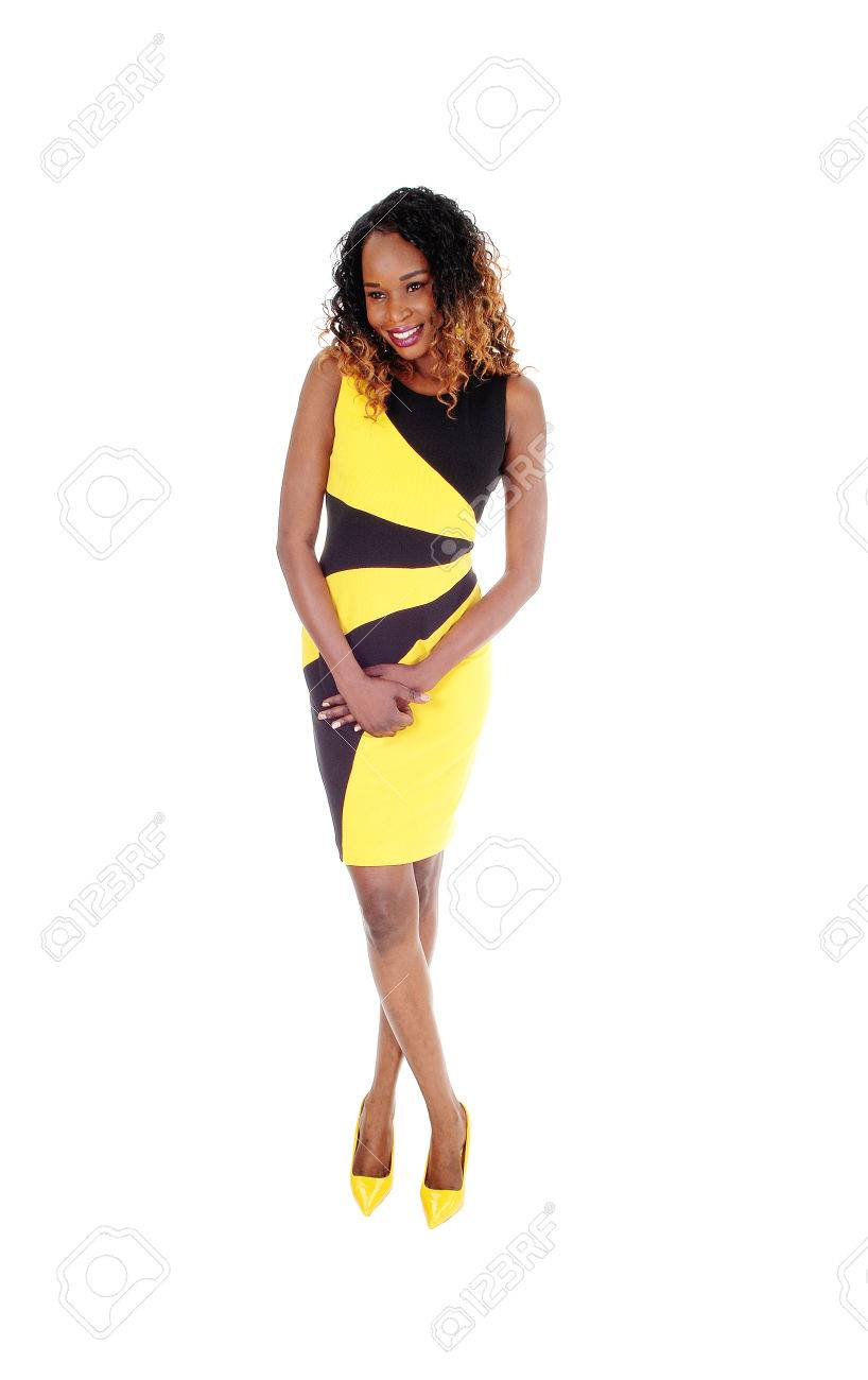 613278c8392 A beautiful African American slim woman standing in a black and yellow dress