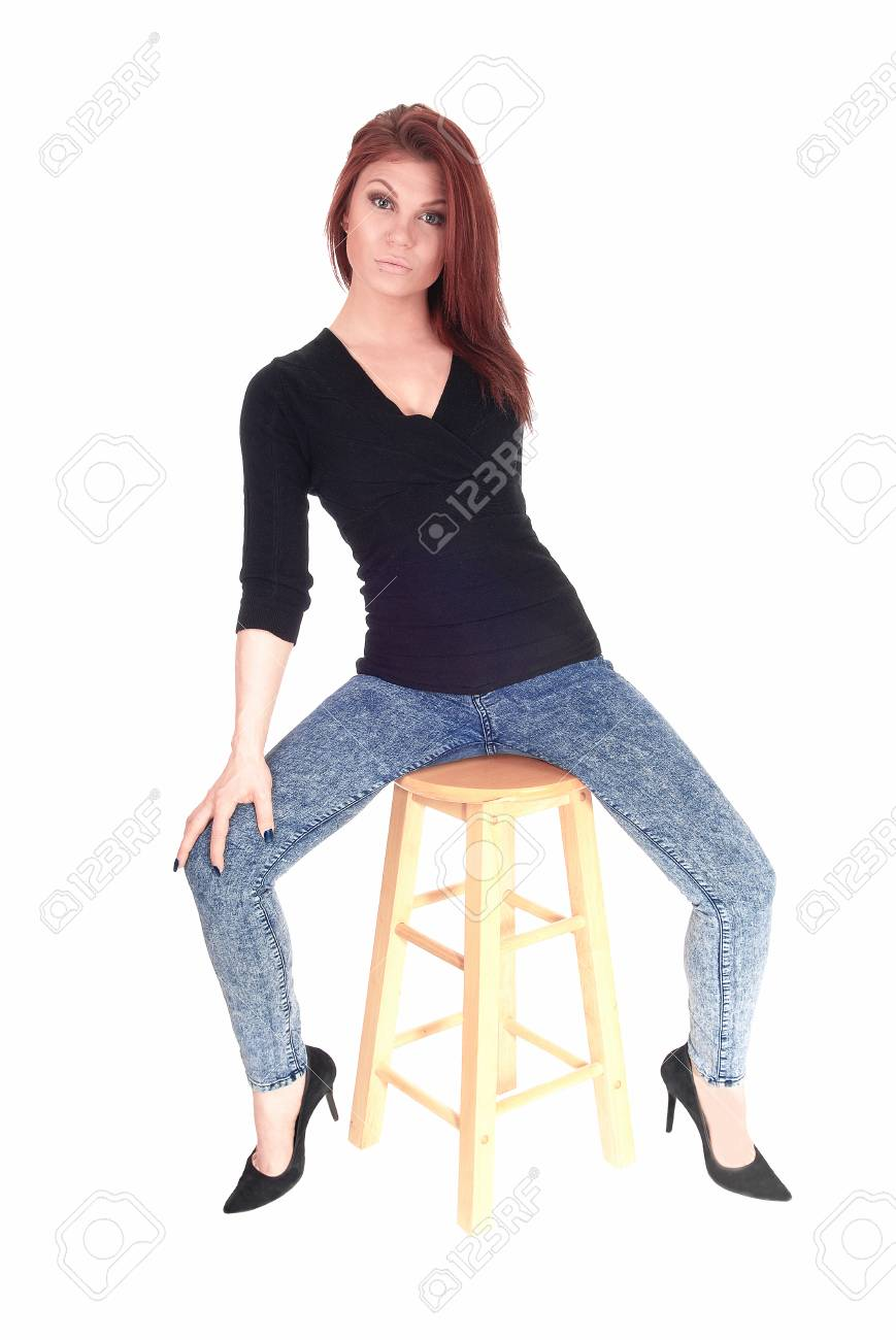 a beautiful young woman in jeans and a black sweater sitting.. stock