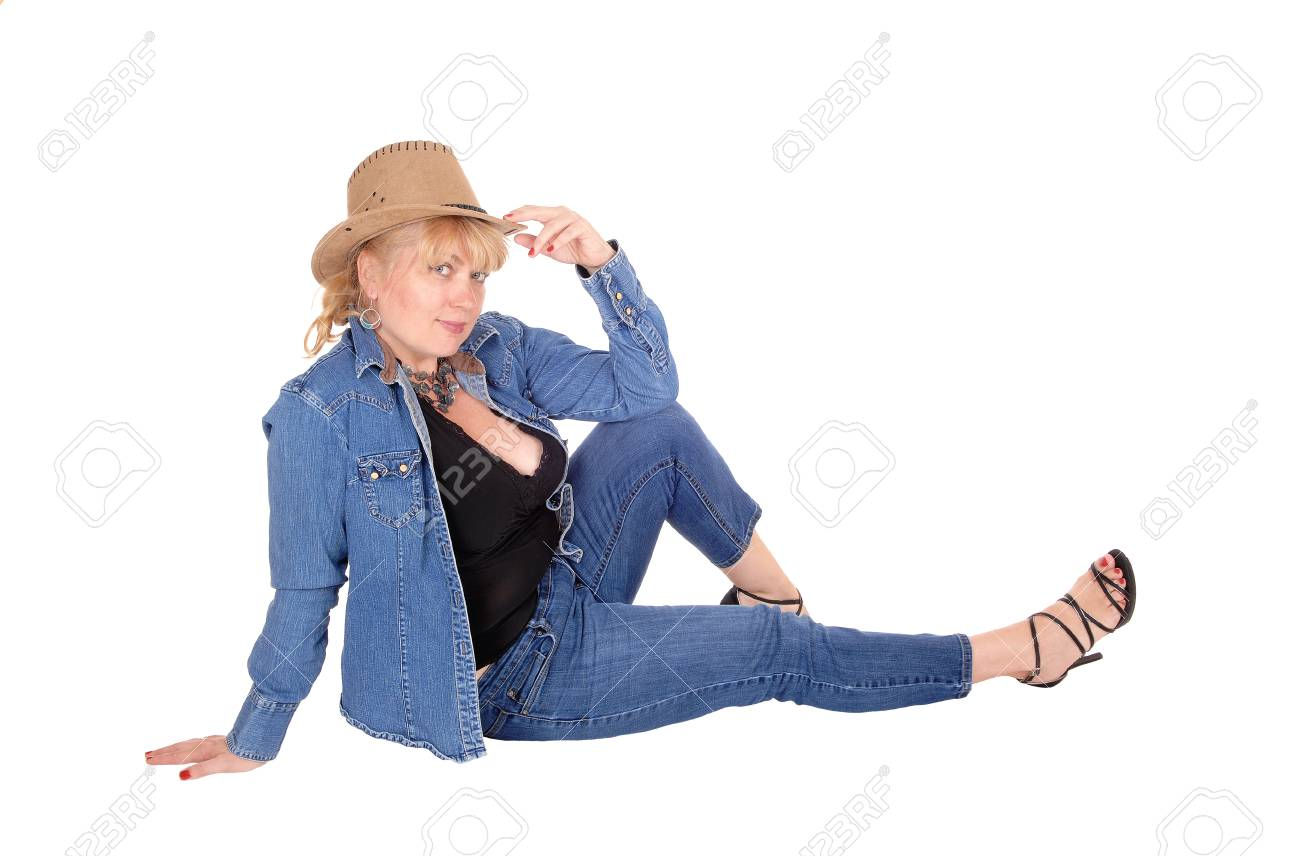 A beautiful young blond woman sitting in a jeans jacked and pants with a cowboy  hat 2900e9da51ee