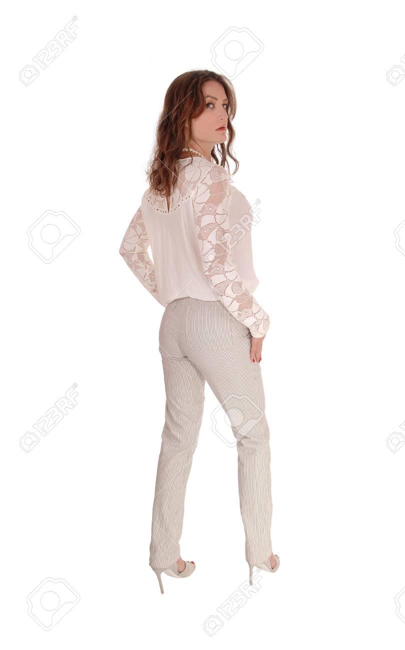 Una Hermosa Mujer Joven En Una Blusa De Encaje Y Cabello Castano Permanente En Pantalones De Vestir De La Parte Posterior Aislado Para El Fondo Blanco Fotos Retratos Imagenes Y Fotografia De