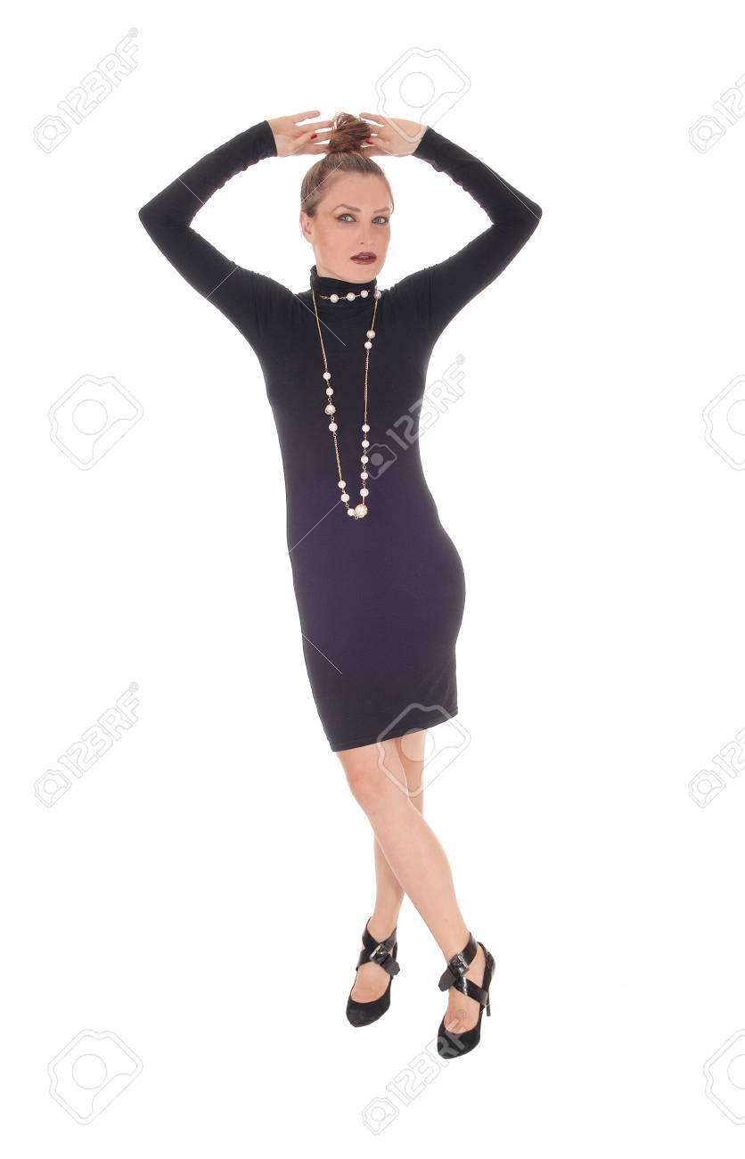 Una Hermosa Joven Caucásica En Un Vestido Negro Y Un Collar Con Los Brazos Hacia Arriba Sobre Su Cabeza Aislada Para El Fondo Blanco