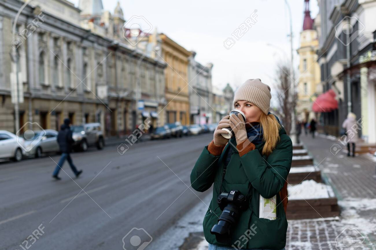 Girl in winter clothes with camera and map in the historical center of the city is holding a cup of coffee on the street - 138325816