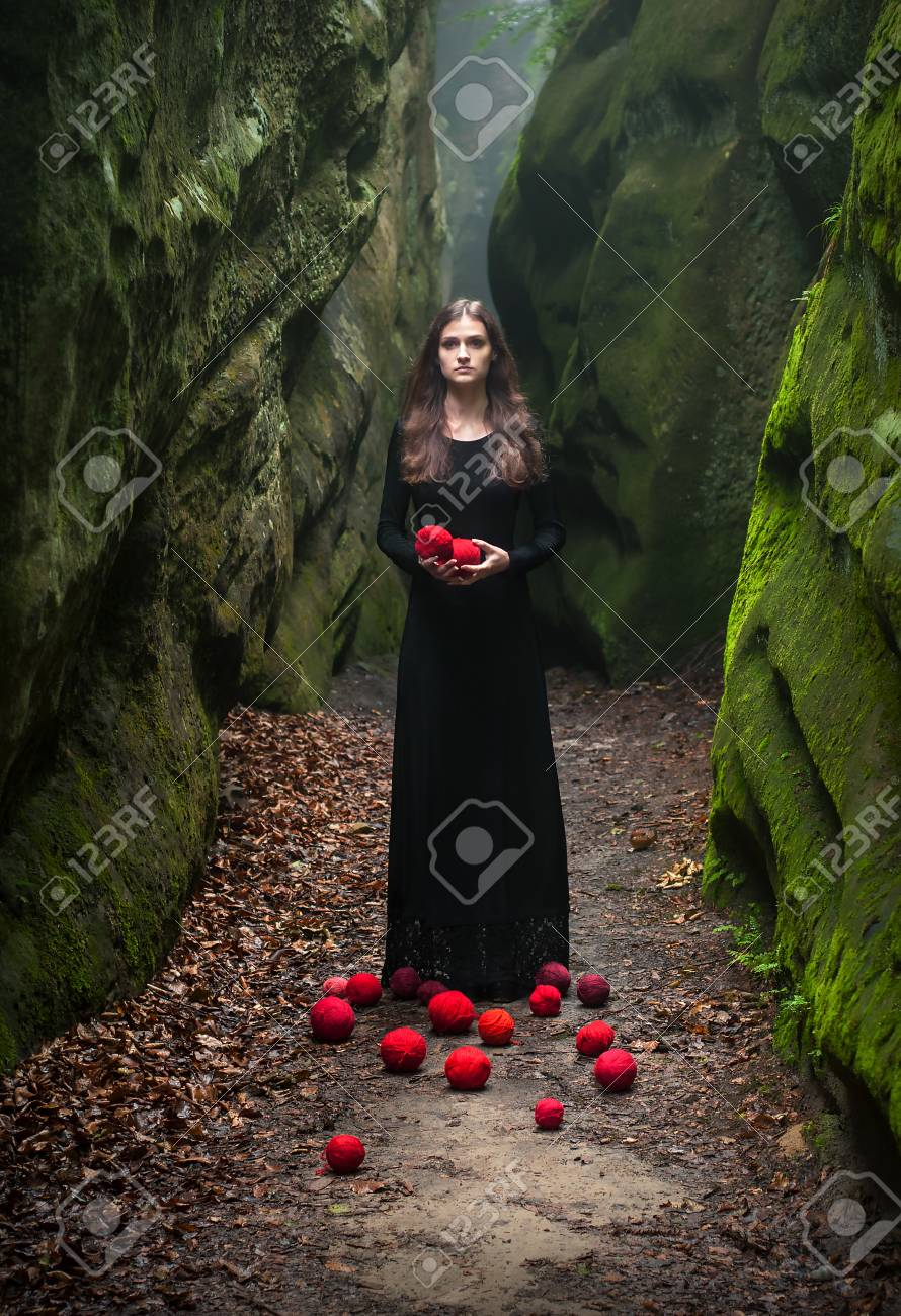 Alone beautiful girl in a fairy forest on the background of stones overgrown with moss portrait of a brunette in a black dress that stands near the rocks
