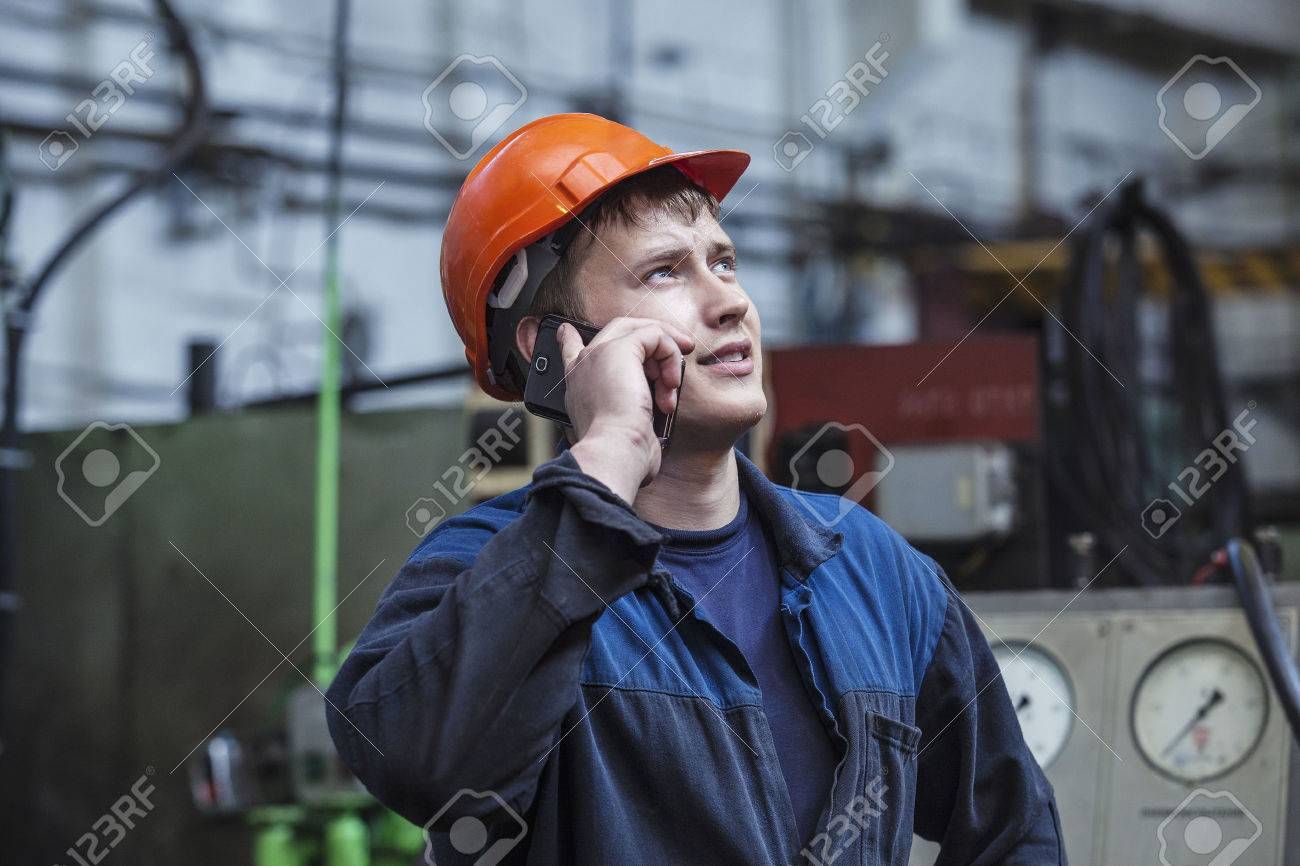 The young man working at the old factory on installation of equipment in a protective helmet - 40821854
