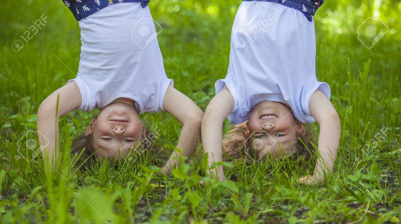 Children standing in a meadow on the hands on the green grass - 40824245