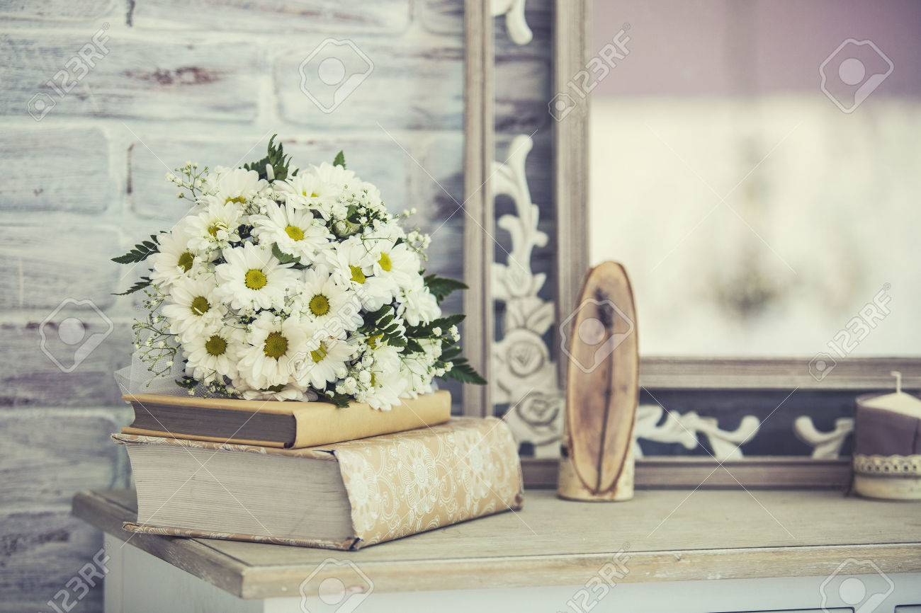 Wedding Bouquet Of Daisies On A Stack Of Books On A Shelf Stock