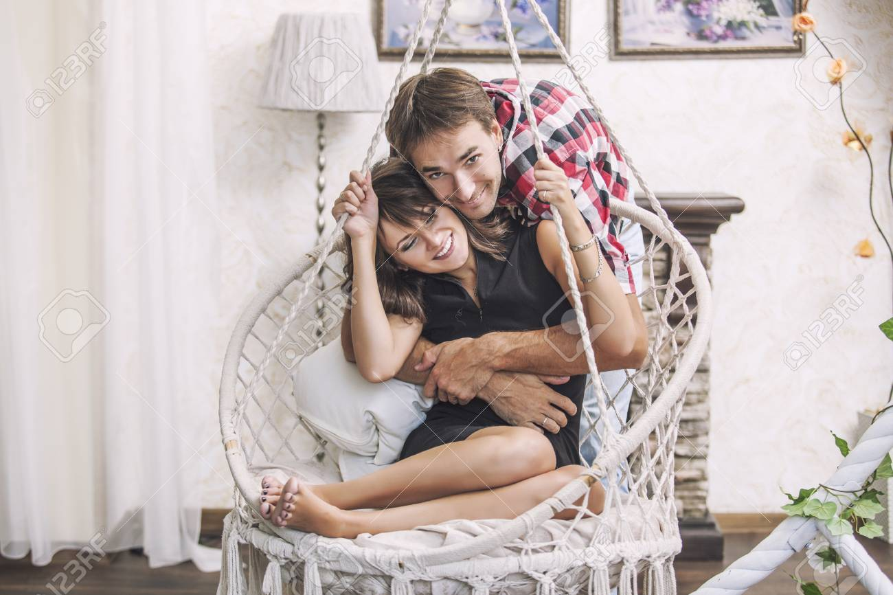 Couple man and woman in a hanging chair cuddling at home - 47974729