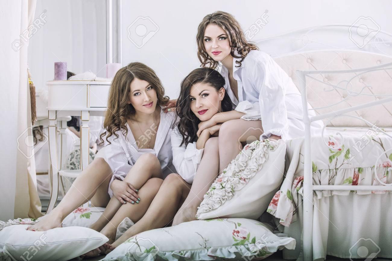 a52ee21d81b Foto de archivo - Tres hermosas mujeres jóvenes amigos en el chat en el  dormitorio con camisas blancas