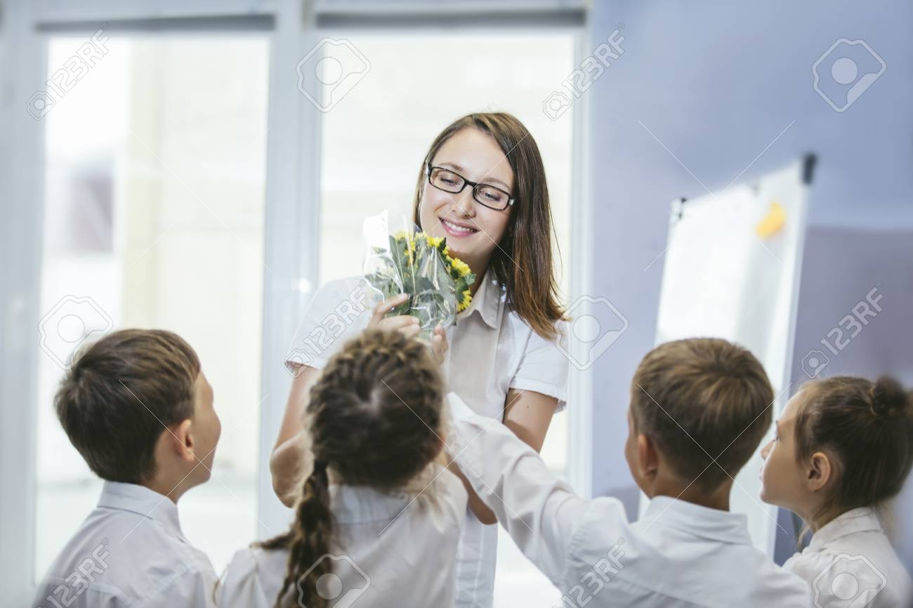 Beautiful children school children with flowers for the teachers at school on a holiday - 84430054