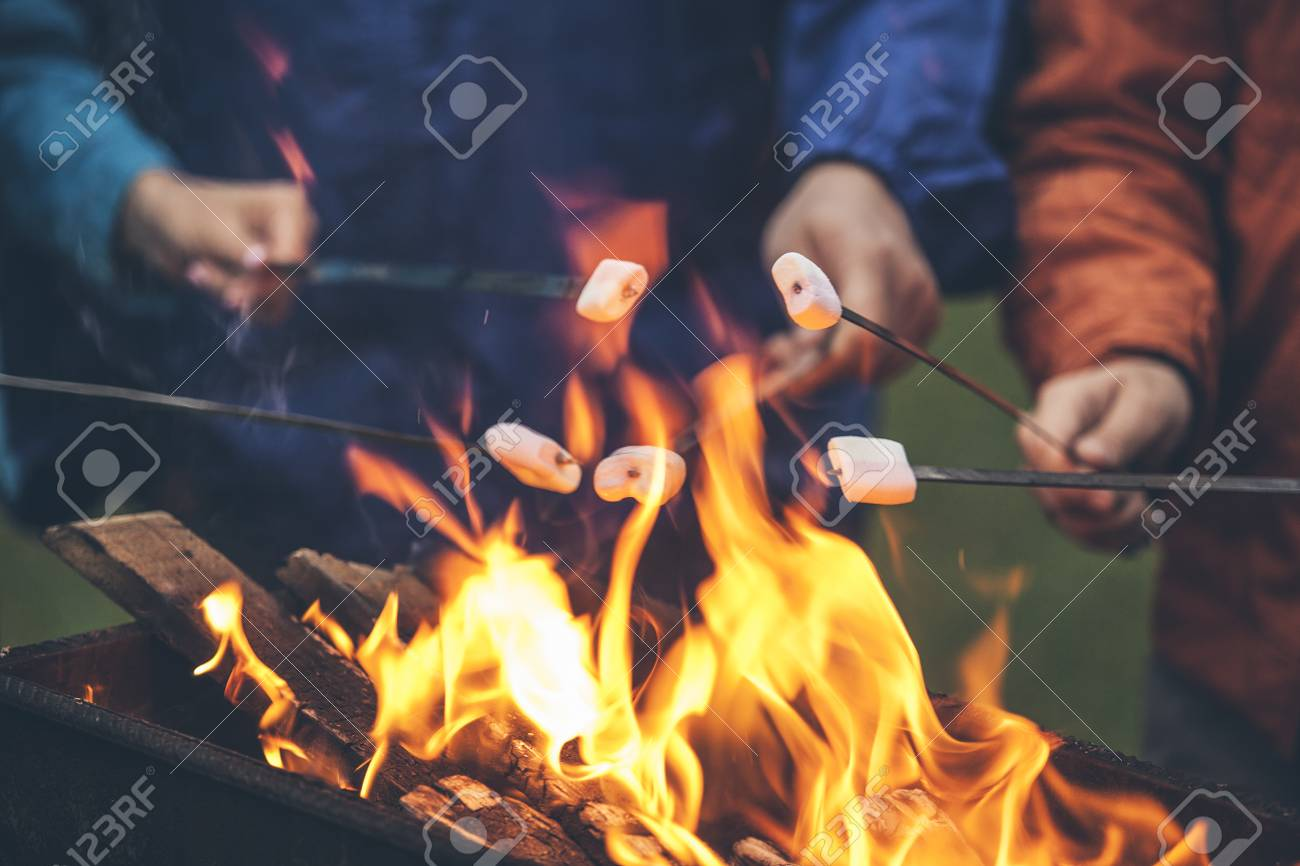 Hands Of Friends Roasting Marshmallows Over The Fire In A Grill Closeup Stock Photo