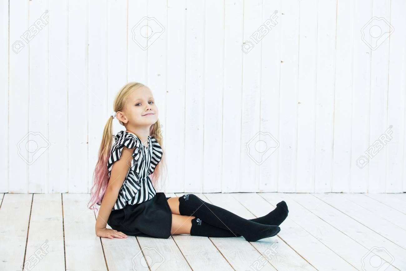 Little beautiful child girl stylish and fashionable on white wooden background - 117673200
