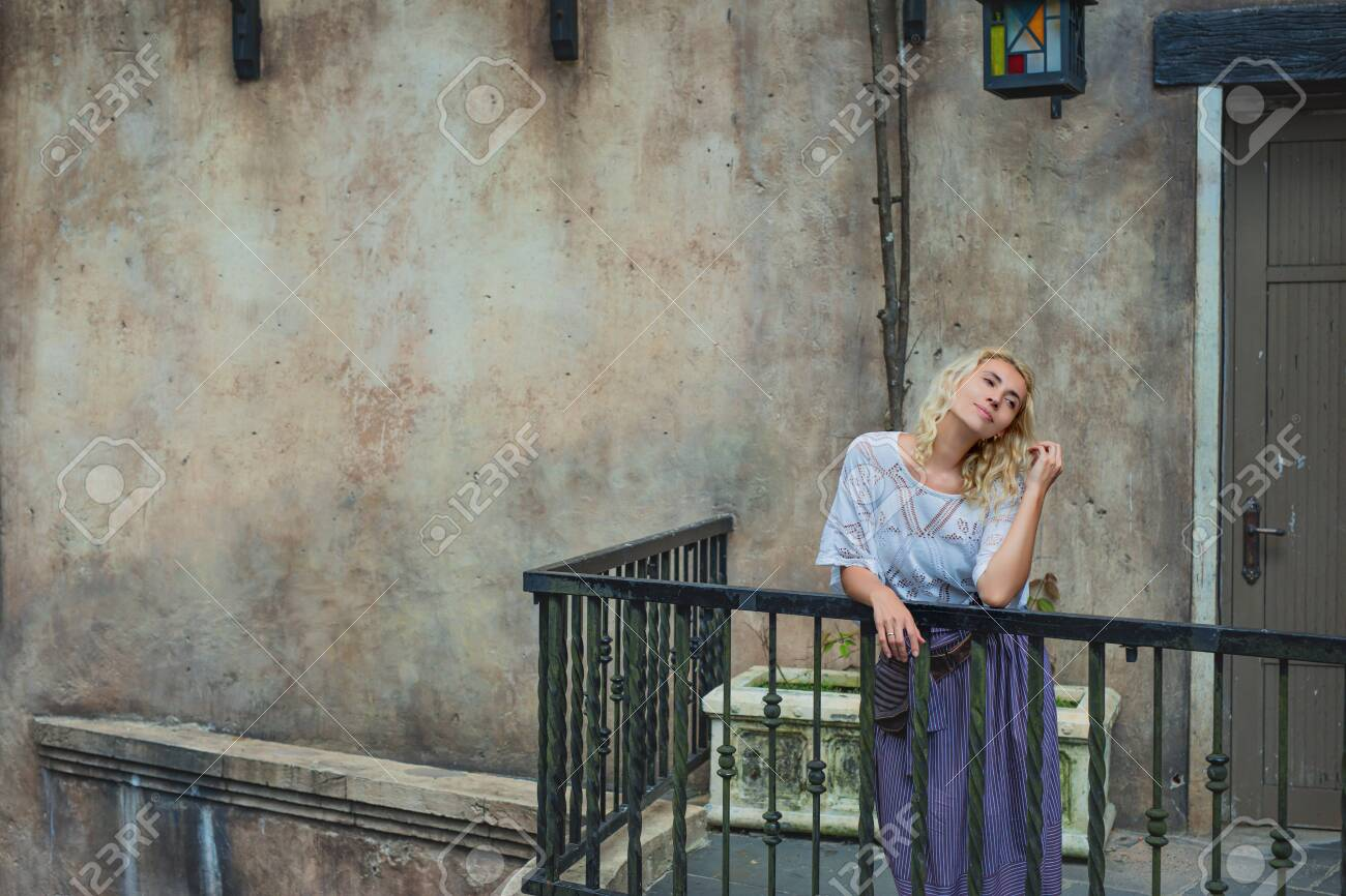 Woman young adult beautiful and happy stands on a balcony against an old wall - 146945692