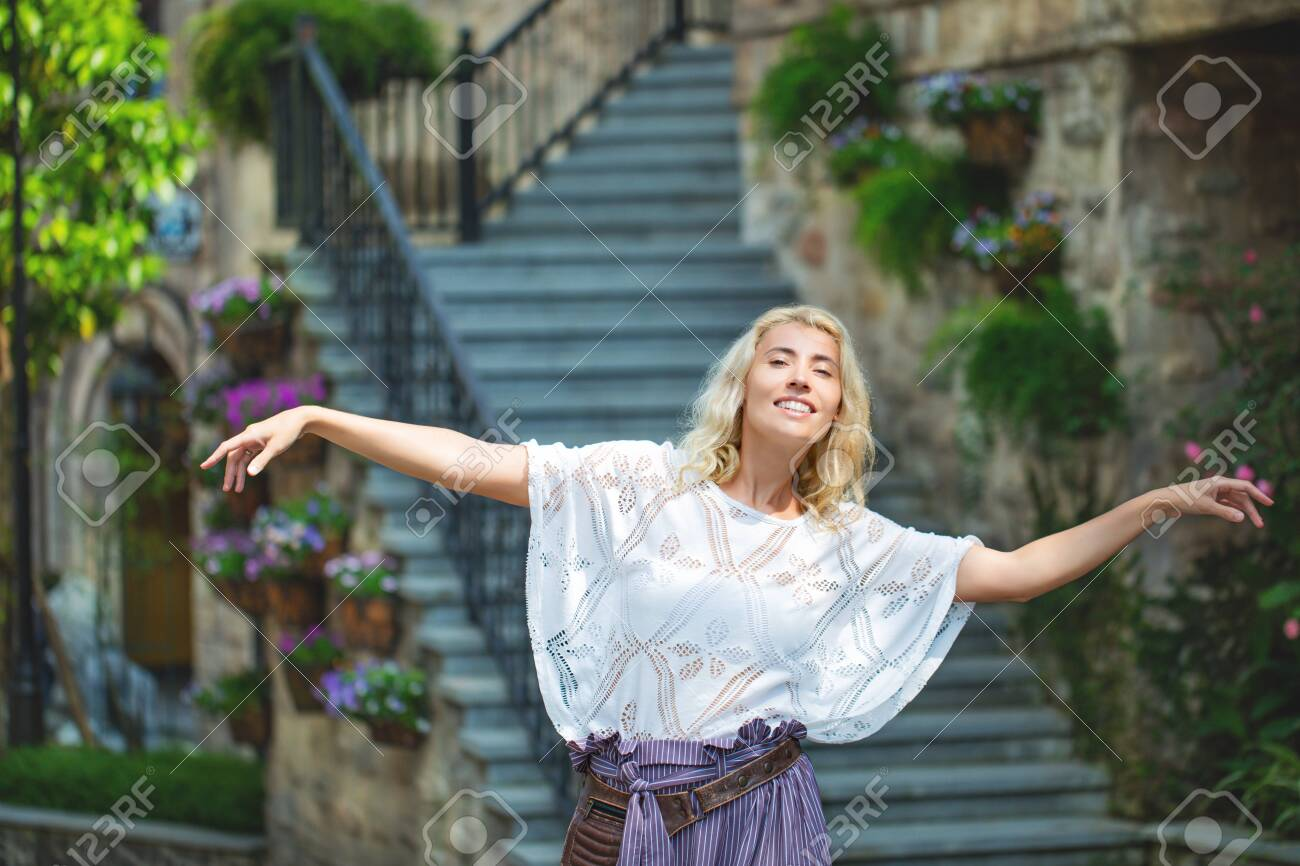 Woman adult young beautiful and happy blonde on the background of stairs on the street of a European city - 146945700