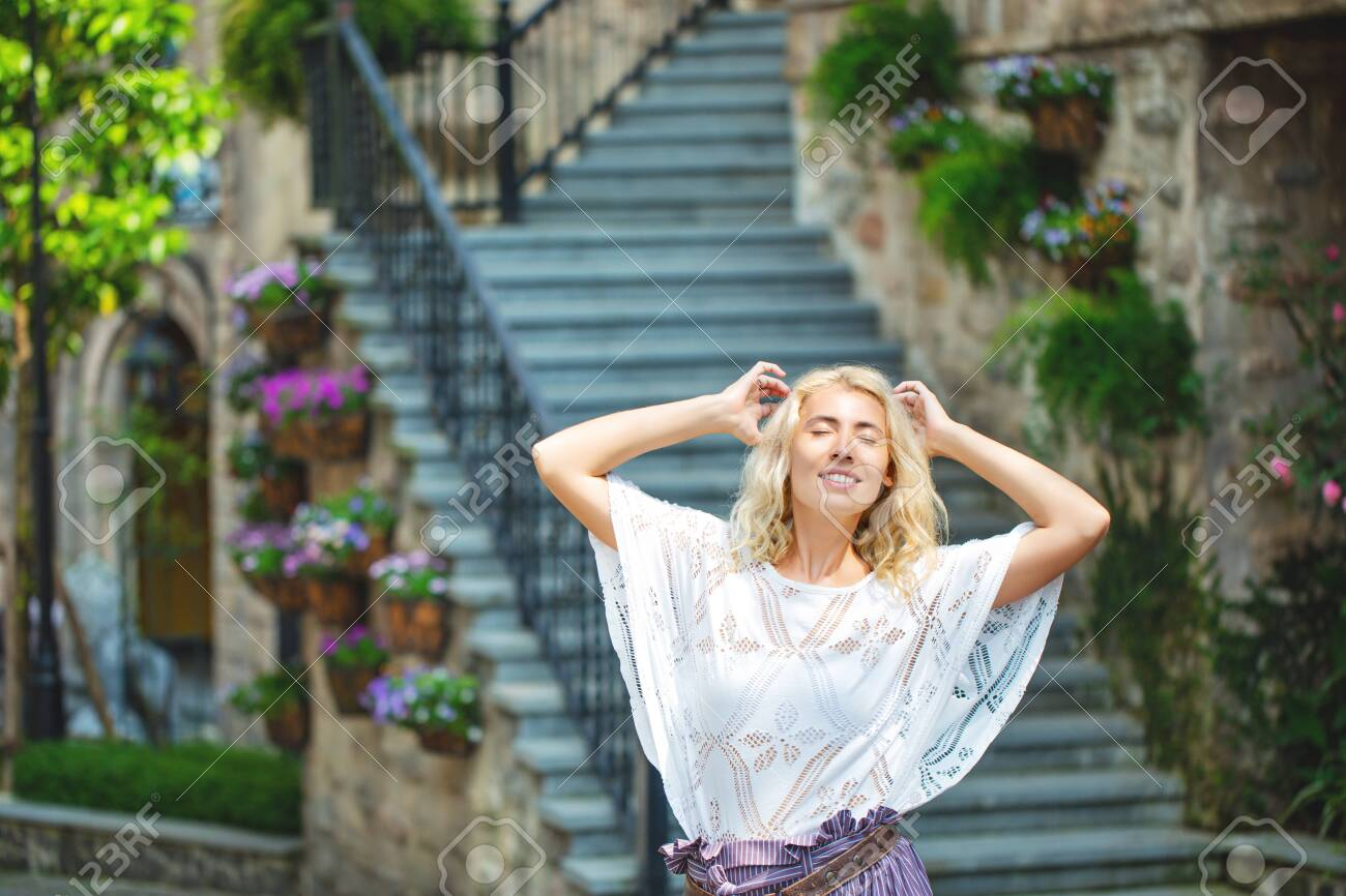 Woman adult young beautiful and happy blonde on the background of stairs on the street of a European city - 146945704