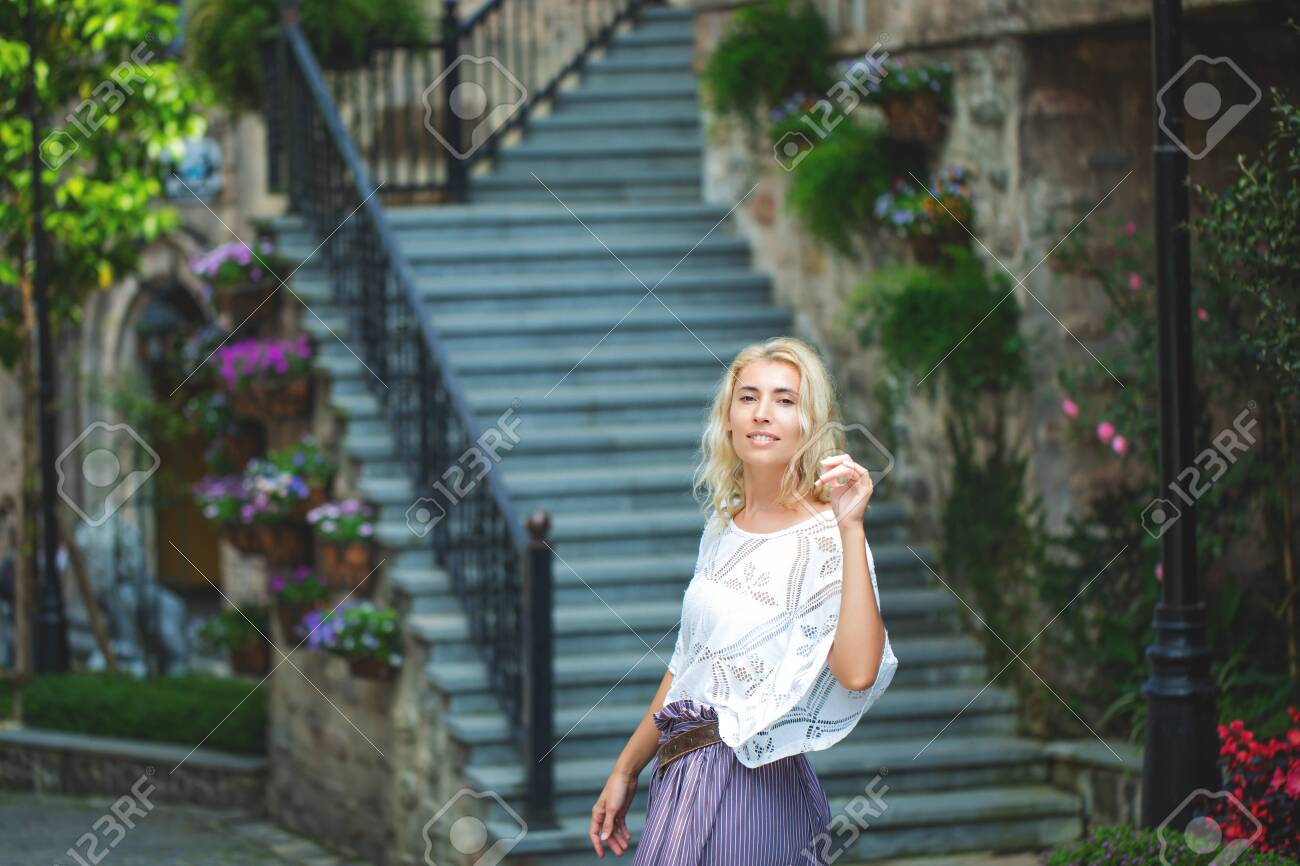 Woman adult young beautiful and happy blonde on the background of stairs on the street of a European city - 146945707