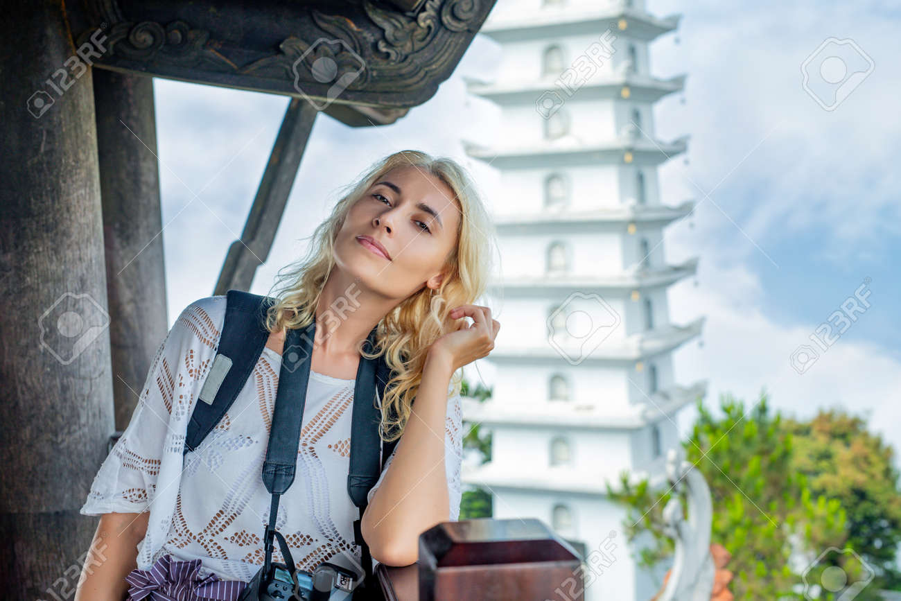 Female tourist young adult beautiful against the background of a white Buddhist temple - 146945714