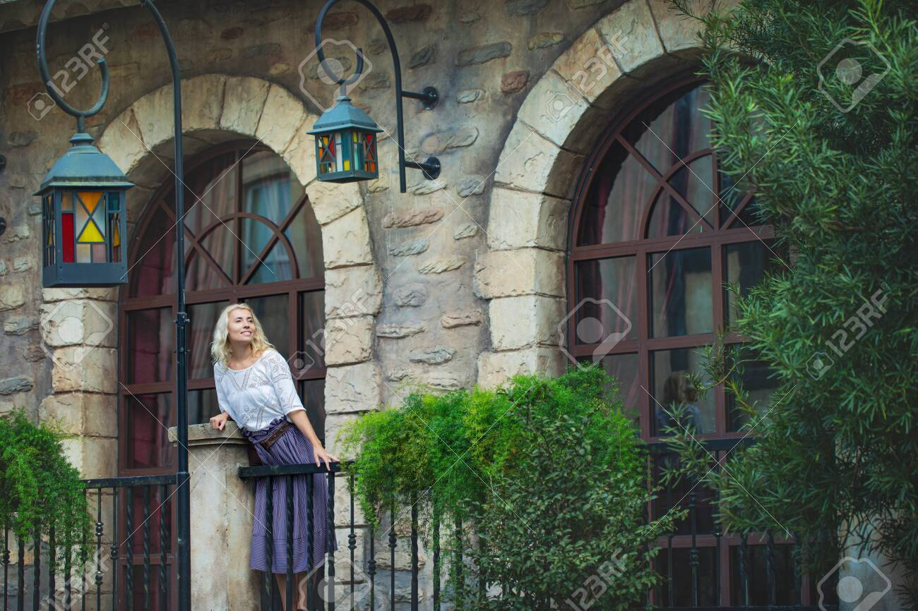 Woman an adult young beautiful and happy blonde on the balcony of an old beautiful European house - 146945715