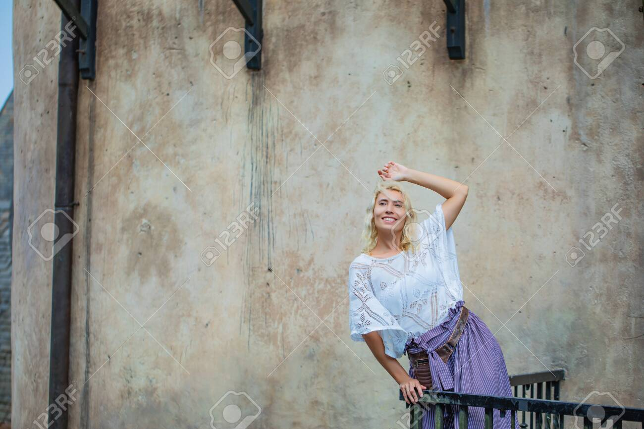 Woman young adult beautiful and happy stands on a balcony against an old wall - 146945716