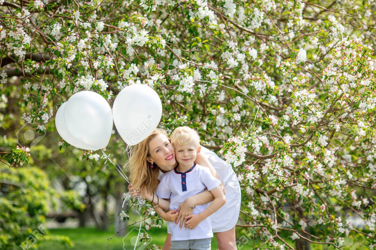 Family mother and son, beautiful and happy with balloons on the background of a blooming Apple tree - 147451828