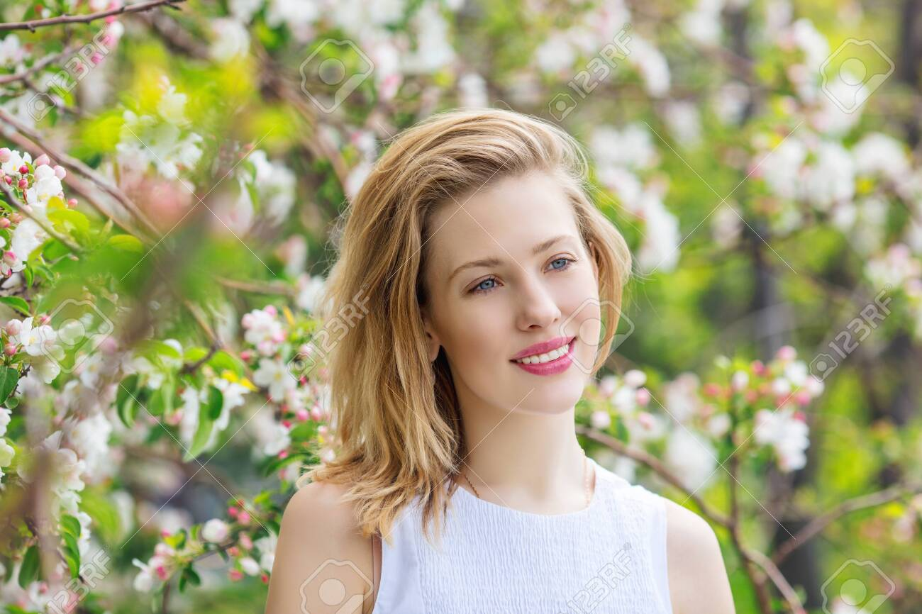 Beautiful young and happy woman close-up portrait on the background of a blooming Apple tree - 149002199