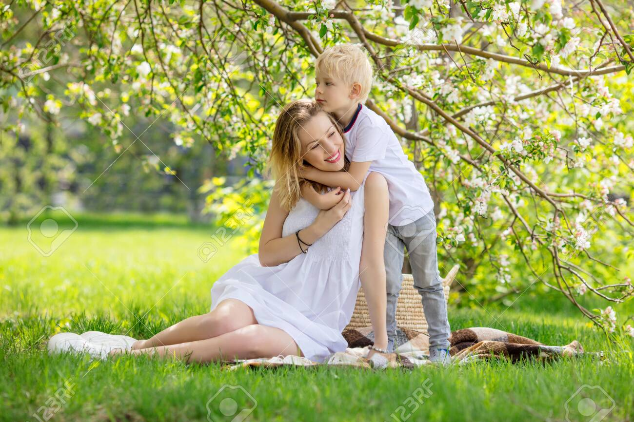 Family mother and son, beautiful and happy together sitting on the grass in front of a flowering Apple tree - 147451953