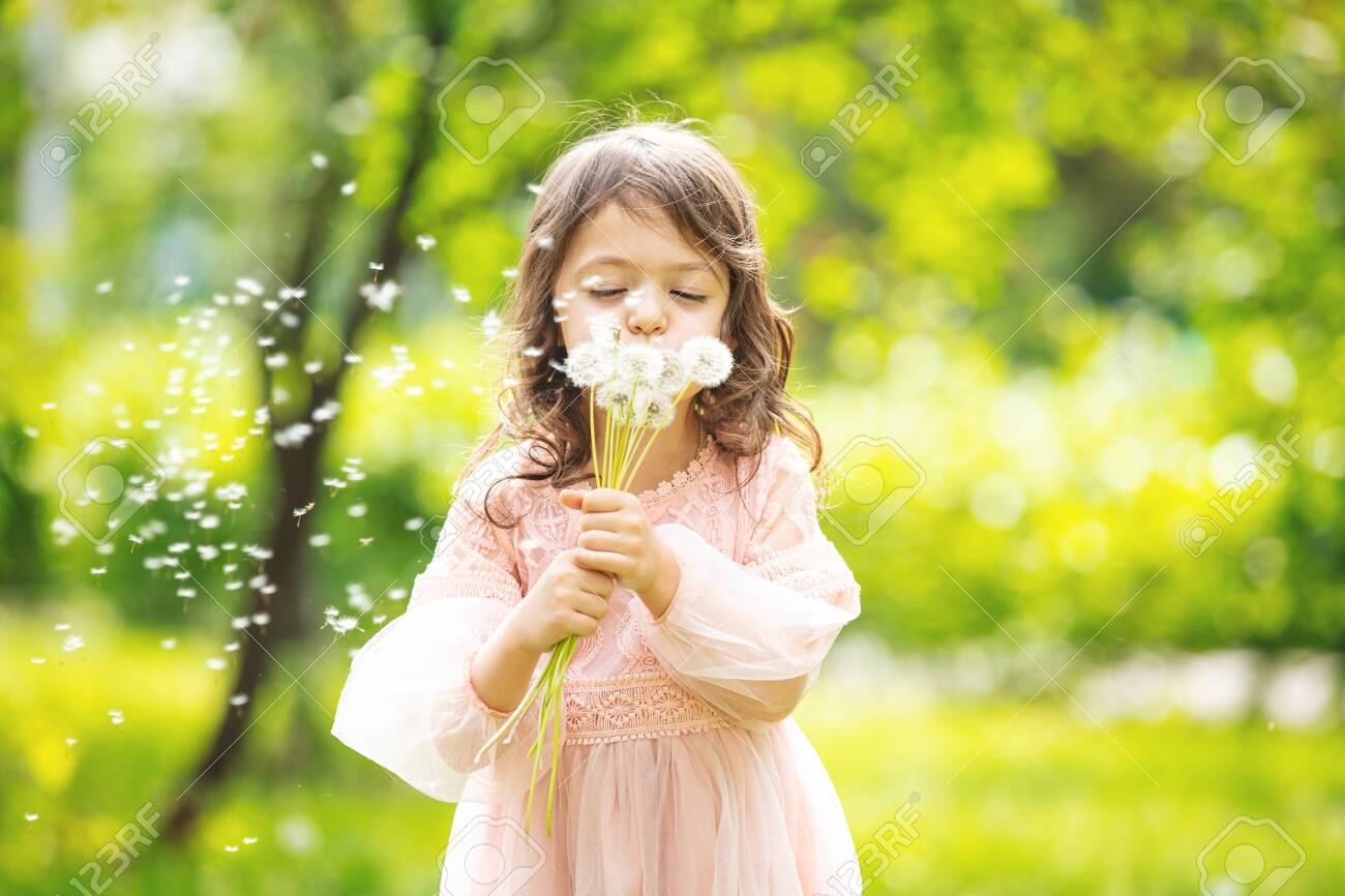 Little girl child cute and beautiful with a bunch of dandelions blowing on them in nature - 148102867