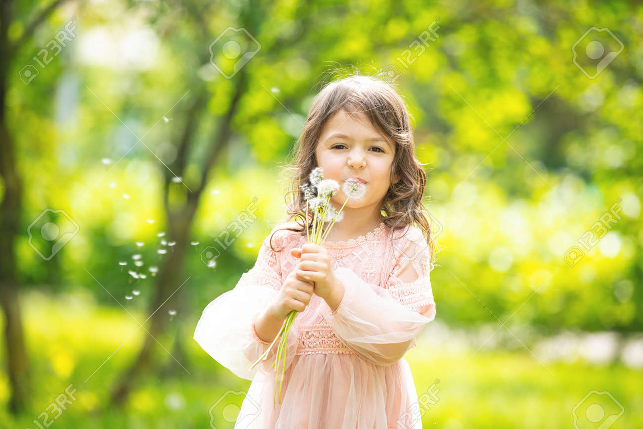 Little girl child cute and beautiful with a bunch of dandelions blowing on them in nature - 148103547