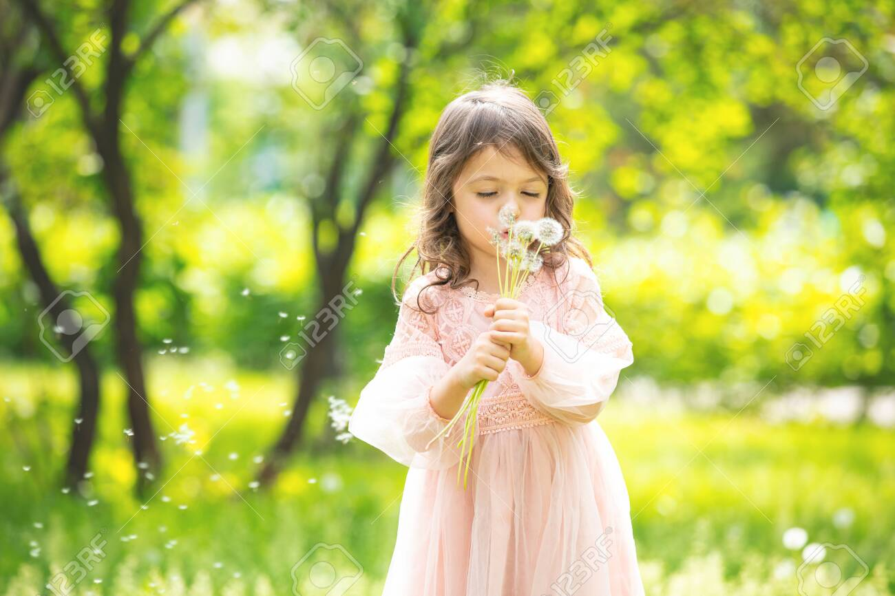Little girl child cute and beautiful with a bunch of dandelions blowing on them in nature - 148102715