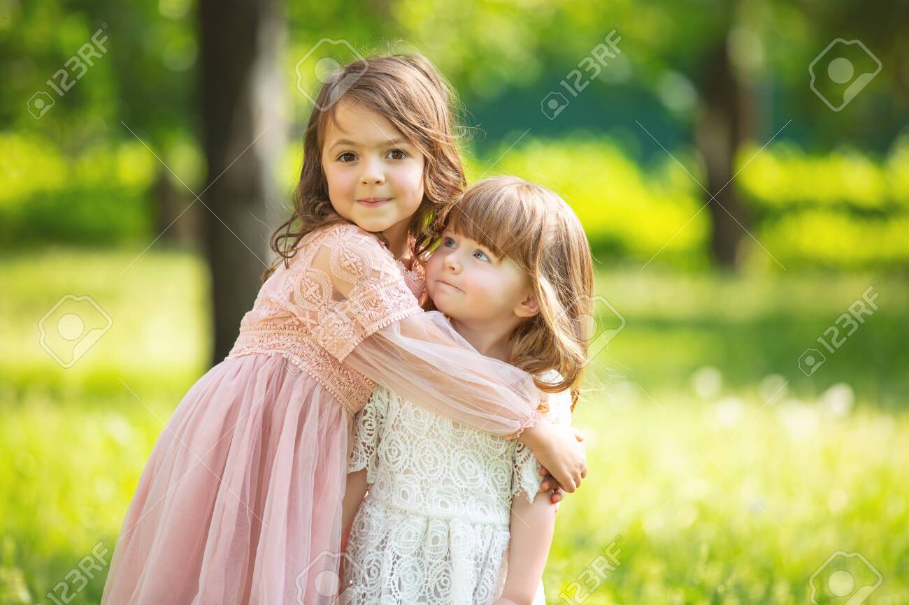 Two small beautiful girls children together happy play and laugh in nature - 149471276