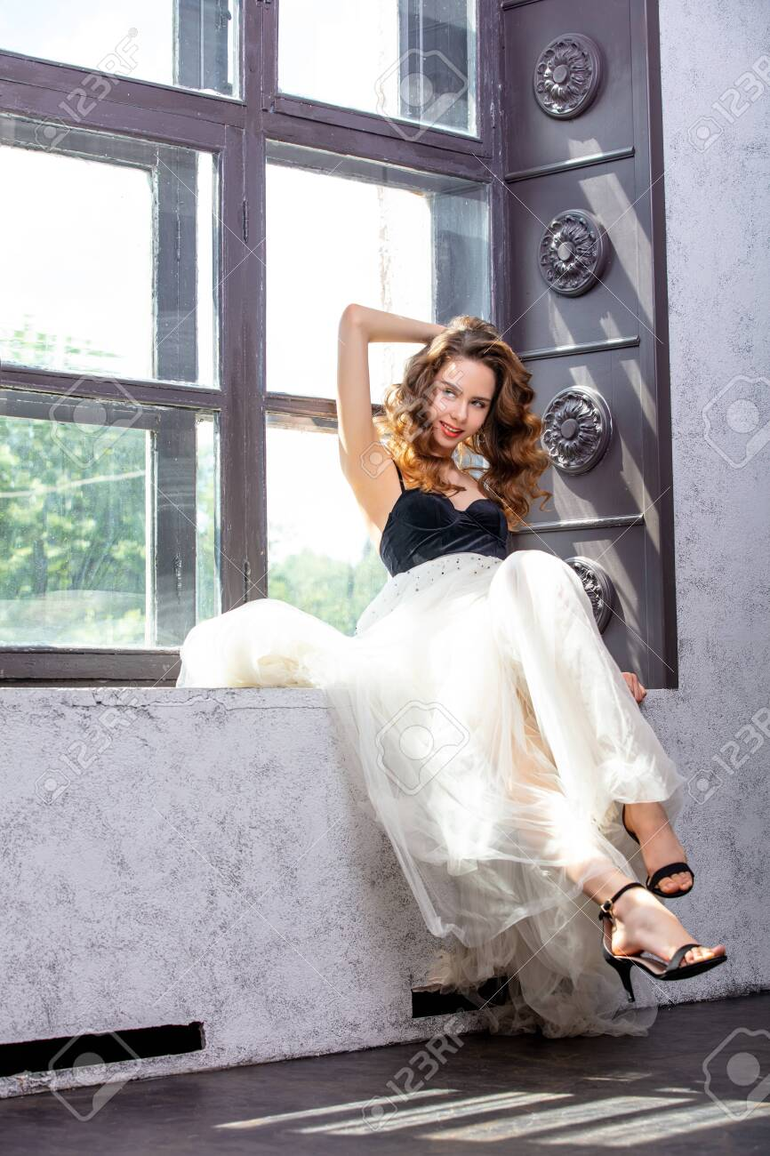 Beautiful luxurious young girl model with makeup and brown curls on the window in an airy skirt - 150022051