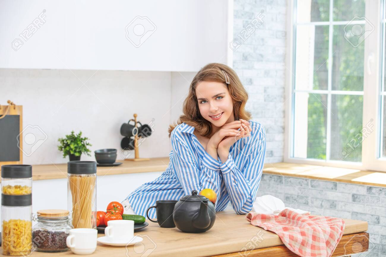 Beautiful and cute young girl at home in the kitchen in casual clothes - 150022054