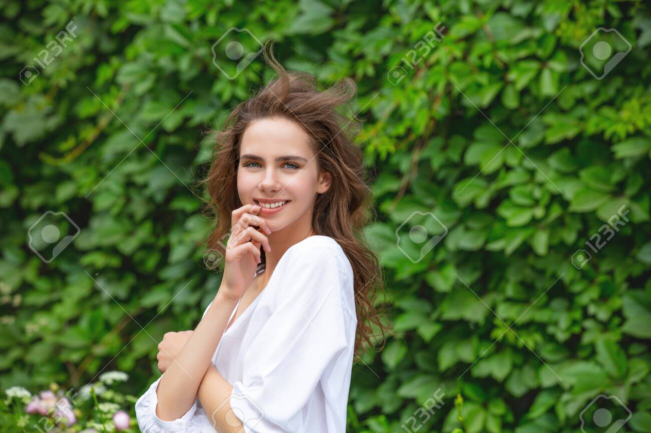 Beautiful and cute young girl in the summer in the Park against a green wall with plants - 150022056