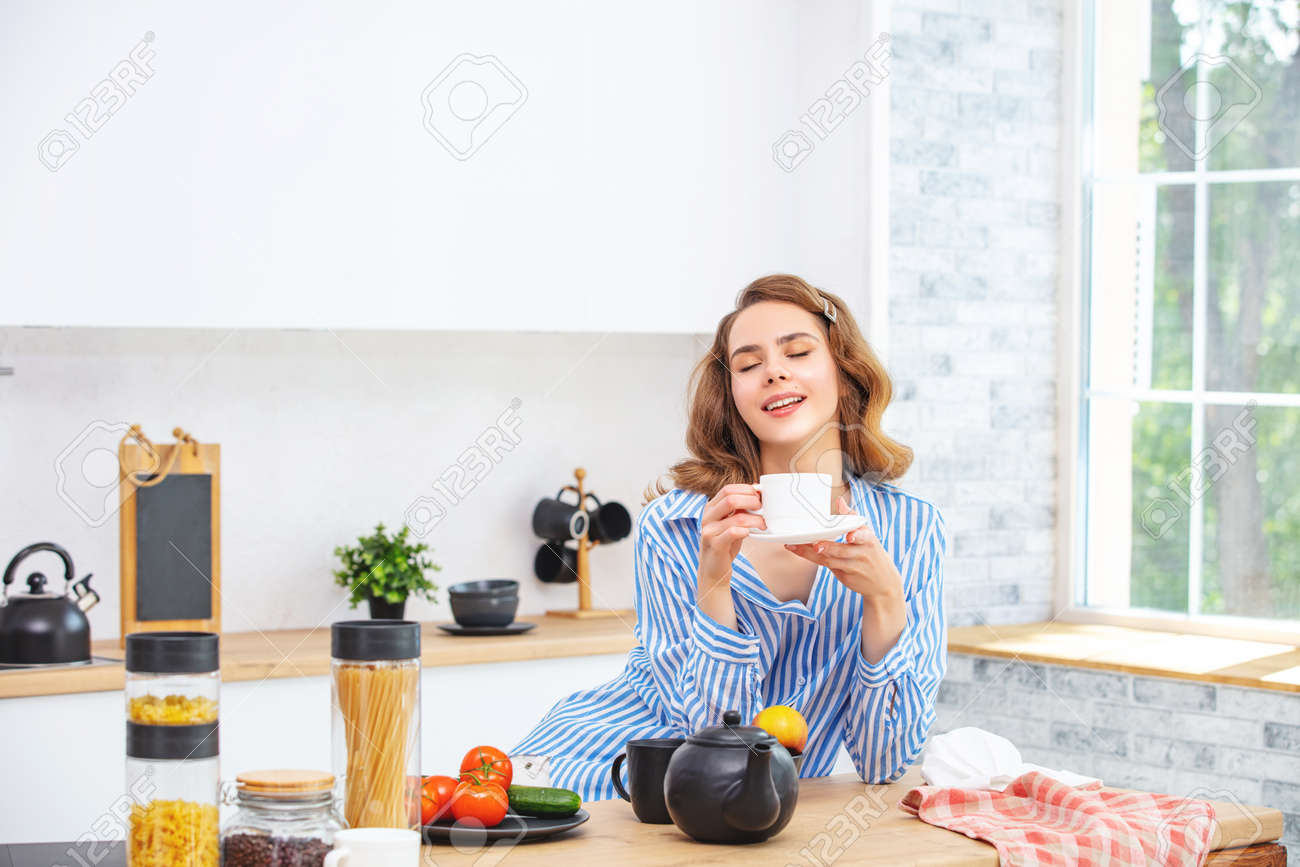 Beautiful and cute young girl at home in the kitchen with a Cup in her hands in everyday clothes - 150022059