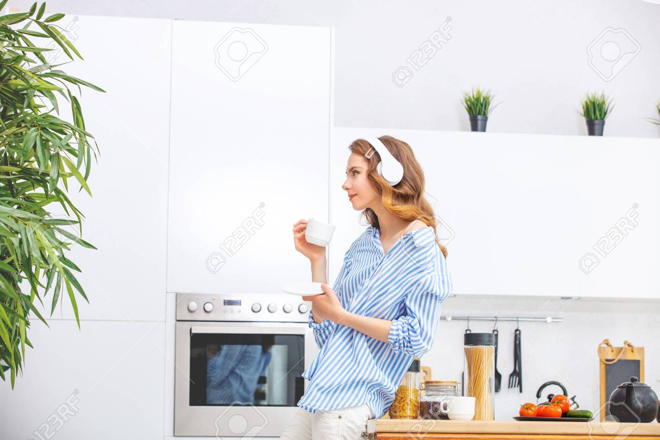 Beautiful and cute young girl at home in the kitchen listening to music with a Cup in her hands and headphones - 150022060