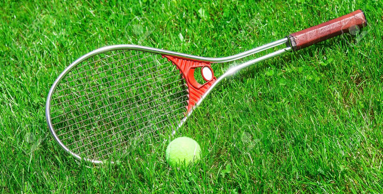 Tennis ball and racket on the green grass of the court close-up - 127068287