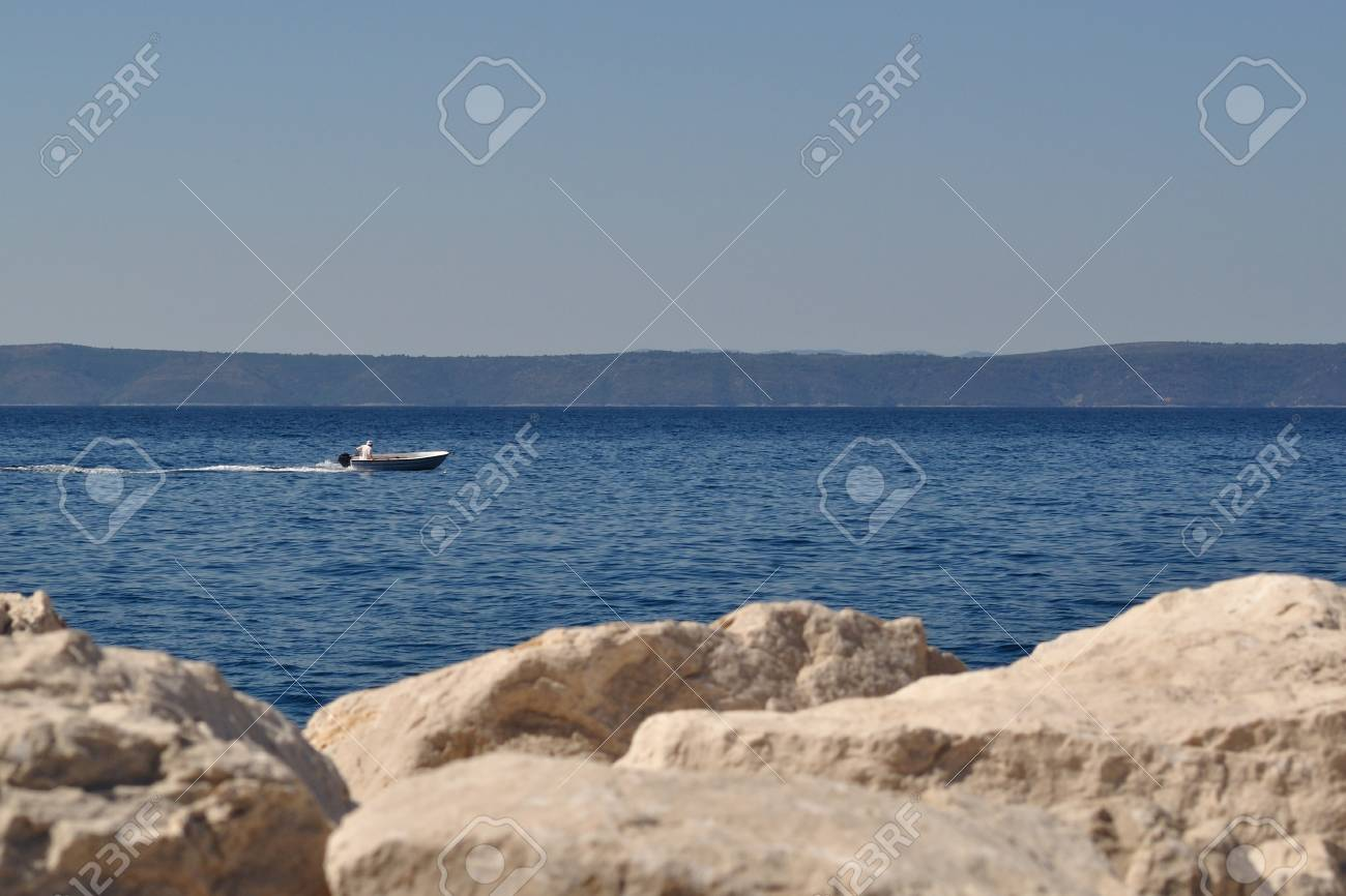 Man in boat on the sea, stones in front, island Hvar in background Stock Photo - 16280676