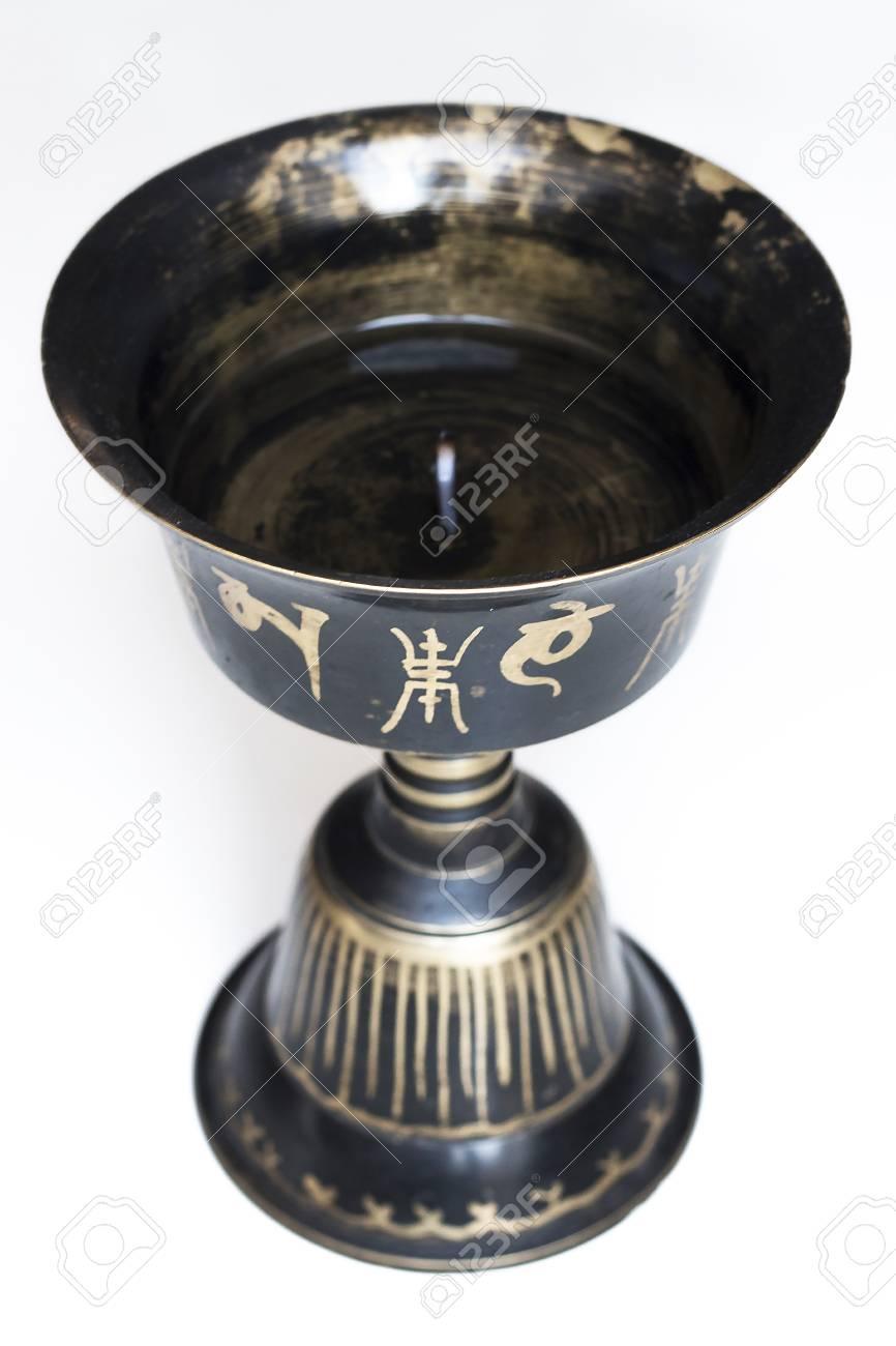 Tibetan buddhist oil lamp close up  Black metal with golden mantras