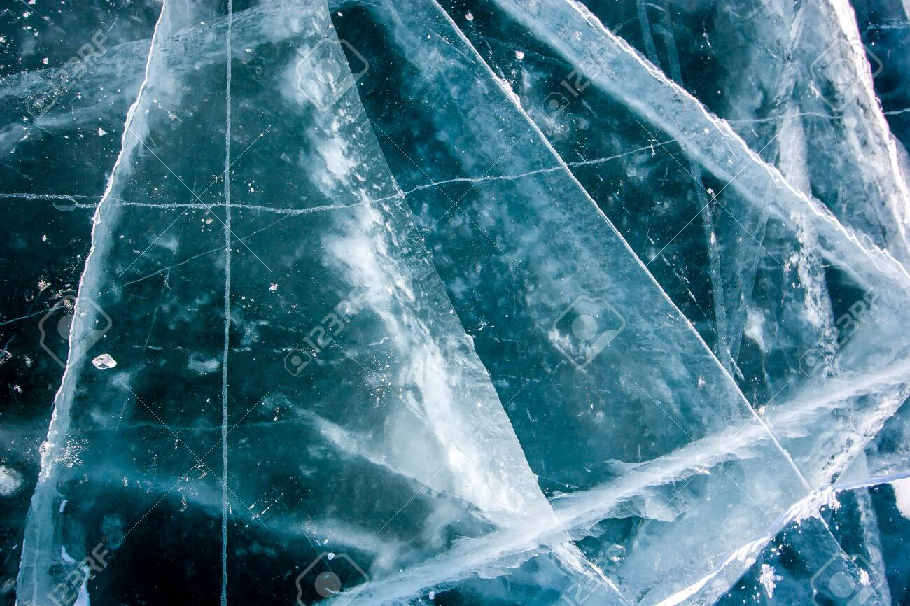 The natural texture of the transparent ice of Lake Baikal with deep cracks. Beautiful winter background. - 133792103