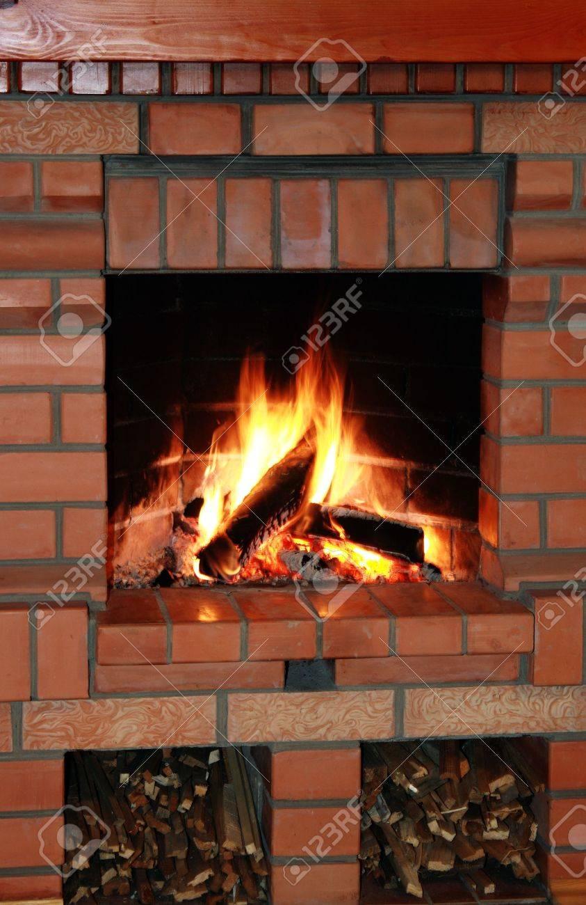 close up of brick fireplace with burning firewood stock photo