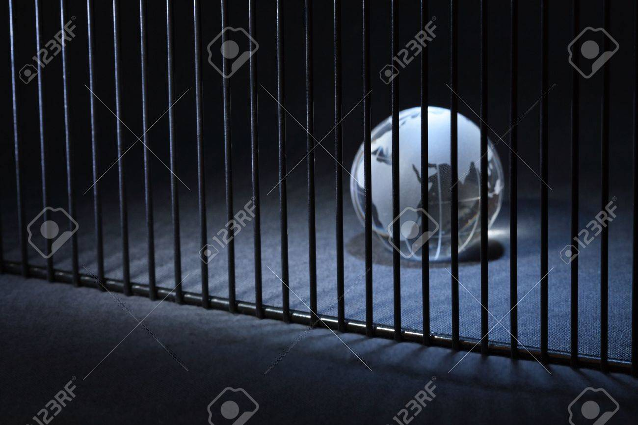 Glass globe behind bars on dark background with copy space Stock Photo - 5618261