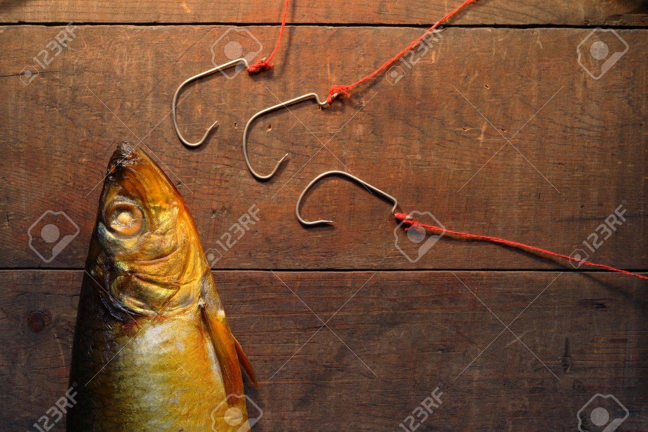 Closeup of bloater near three fishing hooks on wooden background Stock Photo - 8026436