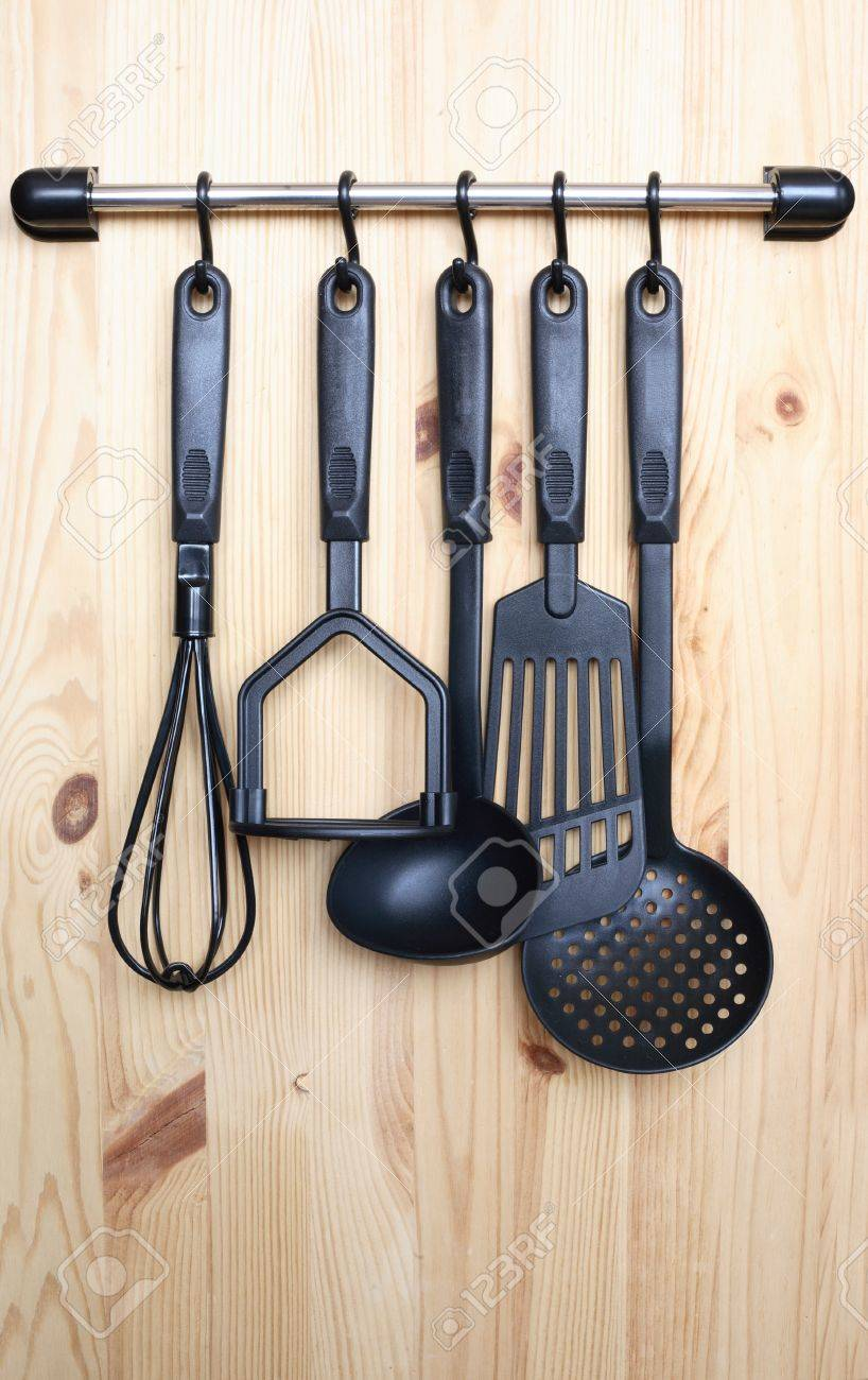 set of black modern kitchen utensil hanging on wooden background