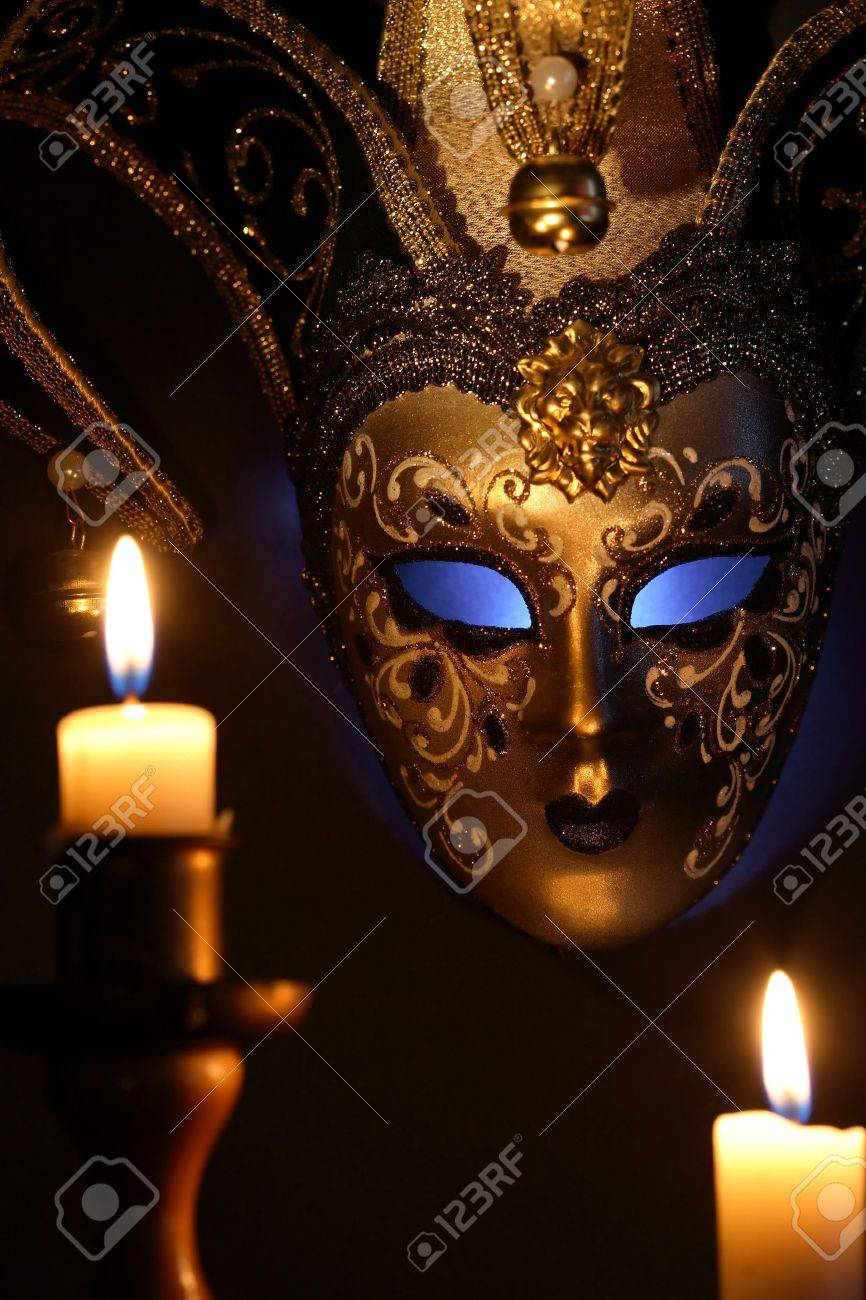Lighting candles against beautiful classical venetian mask on dark background Stock Photo - 15937243